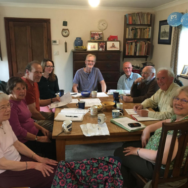 a smiling group of 9 Torridge Green Party members sit around a table